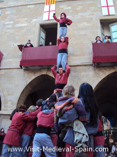 Castellers form a traditional Catalonian human Castle in front of Manresa town hall while the king and royal family look on from the balcony .These towers are typical across Catalonia and are often bigger than the one shown here.