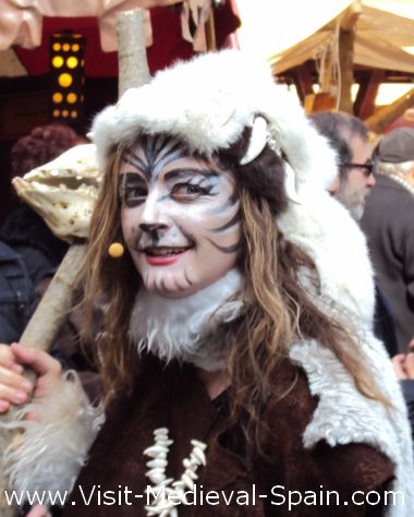 Photo of a young woman dressed as a medieval witch, her face painted to represent a tiger and carrying a sheeps skull, in Manresa's medieval Fair 2011.