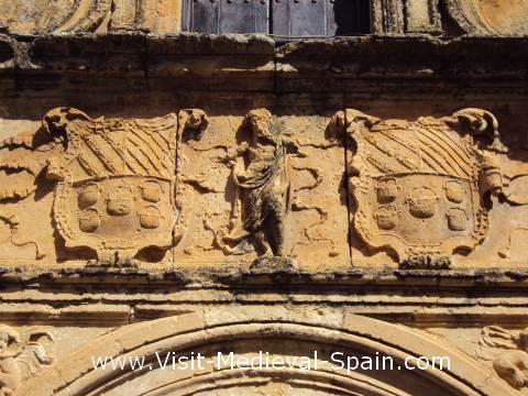 Heavily weathered medieval stone carvings above a doorway, Spain