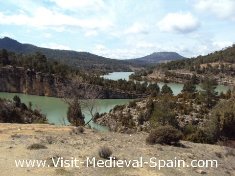 Landscape photo showing the River Jucar surrounded by trees and mountains near to Alarcon, Spain
