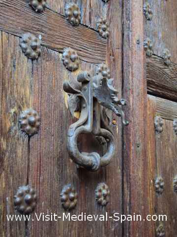 Close up photo of a studded wooden door showing the metal door knocker in the shape of a dragon.