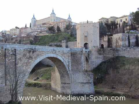 The Puente de Alcantara bridge over the river Tajo with the Alcazar and the old town of Toledo in the background.