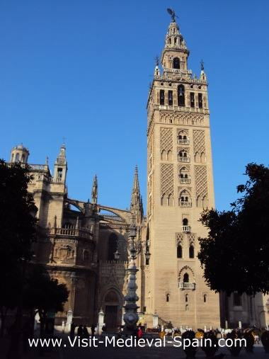 The medieval Cathedral and La Giralda tower in Seville Spain, photo taken on a sunny day with orange trees siuluetted in the forground