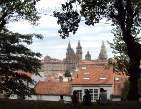 The Medieval Cathedral od Santiago de Compostela, view from the Alameda park with people and trees silueted in the foreground