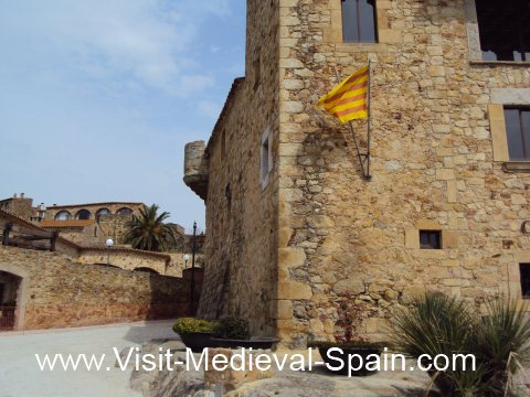 A Catalan flag flying on the side of a medieval stone house in Pals near Girona, Spain