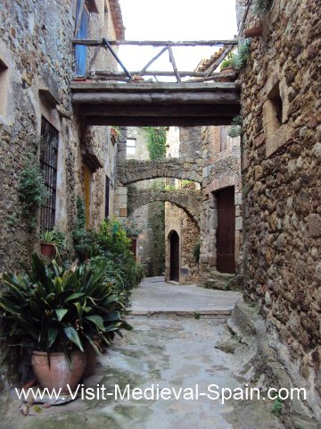 Narrow Street with a bridge and arches between stone houses in the medieval village of Pals, Catalonia.
